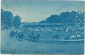 Men in uncovered carriages race their horses around the ring in front of the spectating crowd. (From postcard collection legacy system.)