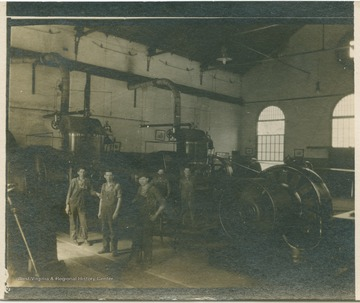 Five workers stand among the machinery at the Kingwood Power Station. (From postcard collection legacy system.)