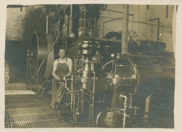 Worker at Kingwood Power Station sits on the machinery. (From postcard collection legacy system.)