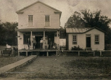 Several men stand on front porch of post office. Small horse and what appears to be a cow to the left of building.