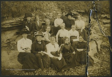 A group of women sitting in a field. See original for full photo roster.