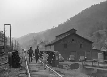 Group of people further down railroad tracks walk in the same direction. Two miners covered in dirt approach the young girl.