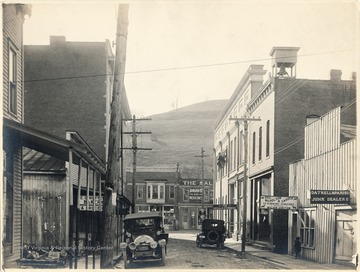 Gatrell and Parish Junk Dealers shop on the right, next to Drs. Nicholson and Carder Veterinary Surgeons, and The Herald Express building. Drug store straight down the street and bakery on the left of Water Street.