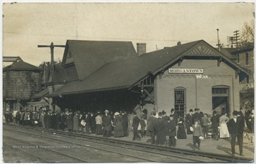 A crowd fills the station center as they wait for the train.