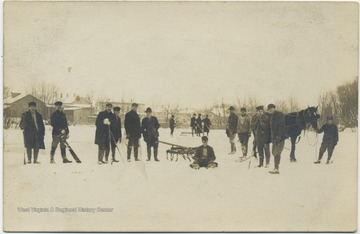 Group of men gather to do work on the ice.