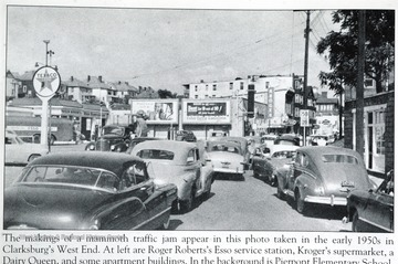 """The makings of a mammoth traffic jam appear in this photo taken in the early 1950s in Clarksburg's West End. At left are Roger Robert's Esso service station, Kroger's supermarket, a Dairy Queen, and some apartment buildings. In the background is Pierpont Elementary School."""