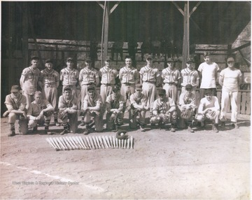 Victorious Hinton baseball team pose behind their neatly lined up baseball bats. Subjects unidentified.