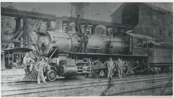 Samuel Irwin leaning on front of the engine. Charles Boley on the running board.