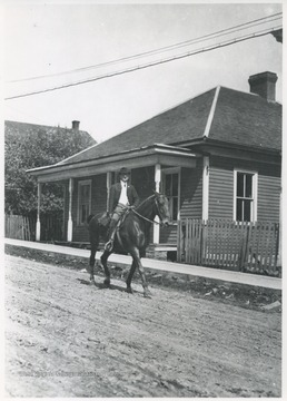 A man rides a horse through the street.