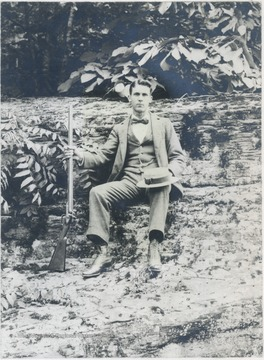 Hight pictured sitting on a log and holding a rifle.
