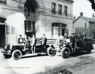 Print number 1265. Trucks are in front of the fire department building on Spruce Street. Doc, the firehouse dog, blends in among the Firemen standing on right vehicle.