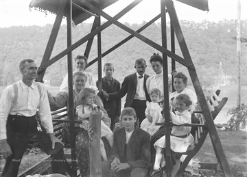 Identified people: Man with mustache on left is Thomas Benton Green, woman on left with child on her lap is Mary Rupert Green, boy in far back is George Green, boy in front is Ray Green, girl holding cat on right side is Virginia Green, and woman next to her is Will Porterfield's wife.