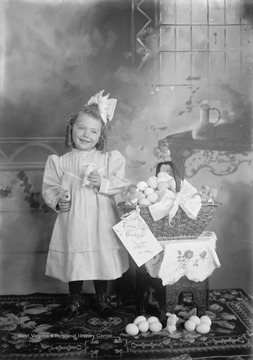 Little girl poses with her stuffed animal bunny next to a basket of Easter eggs.