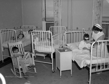 Nurse gives a drink to boy in hospital bed who is wearing a mask covering his eyes after apparent operation.