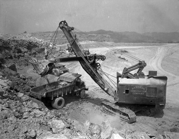 Harrison Construction Company of Pittsburgh, Pennsylvania grading the Kanawha Airport site, circa 1945 or 1946, using a Northwest 80-D shovel to load a Euclid 15-ton capacity rear dump truck with shot rock.