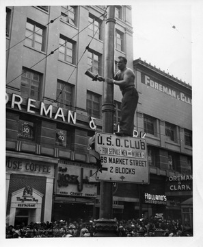 A man stands on a sign up a pole with a fire siren in his hand.