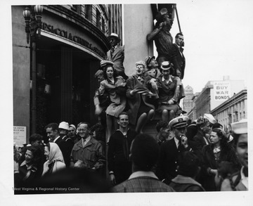 People posing on pillar, celebrating the surrender of Japan during World War II.