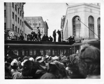 Civilians and Sailors perched the top of a trolley in San Francisco enjoying the celebration of Japan's surrender during World War II.