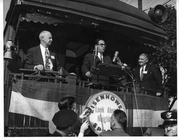Holt delivers a speech from the back of a train during his 1952 campaign for West Virginia Governor. The name of the train was the 'Eisenhower Special', after General Dwight D. Eisenhower who was running for president. Stamped on the back of the photo, ' Photographic Department Weirton Steel Co., Weirton, West Va.'.