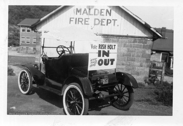 "A car sits by  the Malden Fire Department with a sign that reads ""Vote Rush Holt IN, State House Gang OUT"". The photograph was most likely taken during one of Rush Holt's campaign's for state office."