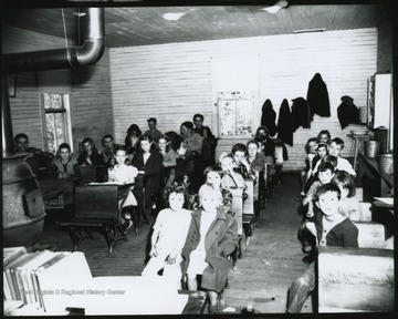 Looking from the front of the classroom, school children of various ages, are pictured sitting at their desks. Subjects unidentified.