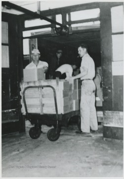 Employees John Smith and Buster Waulaga unloading boxes off of a cart. Company building located on Block C #1.