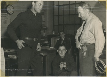 "Starret, left, and Ewing, right, pose in a pretend ""face-off"" with their pistols. Starret starred in western films while Ewing ran the Ritze Theatre. The two men in the background are unidentified."
