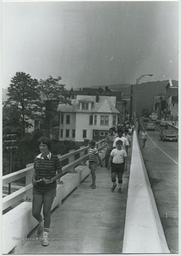 Unidentified people walk along the pedestrian path on the bridge. Old Toll House is pictured in the background on the left.