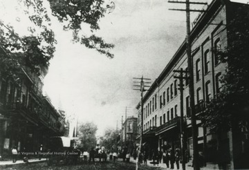 View from Summers Street. People line the sidewalks while a horse-drawn carriage makes its way across the road. Subjects unidentified.