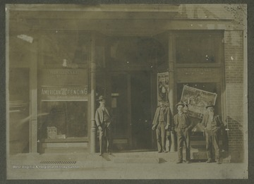 "Four unidentified men pose by the building's entrance. The store windows advertise ""American Field and Hog Fencing: For Sale Here"" and ""The Two Johns"". This is became the location of Danny Foster's in 1986."
