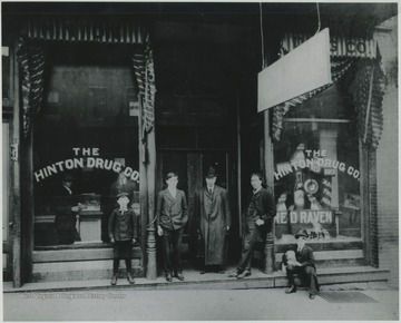 Picture of one of Hinton's early drug stores. It was located next to the First National Bank on 3rd Ave. Wade H. Gwinn, one of the store's operators, is the gentleman leaning against the post on the left. This three-story brick building housed apartments on the upper floors.