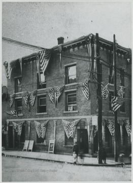 The building, located on the corner of Temple Street and 3rd Avenue, is decorated in American flags.