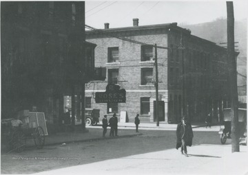 An unidentified man crosses the street. Rose's Drugstore pictured on the left.