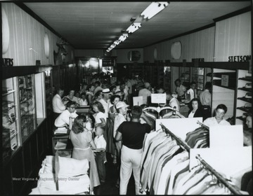 Interior of the store located on Temple St. A crowd of people shuffle through the store and examine the products for sale. Subjects unidentified.