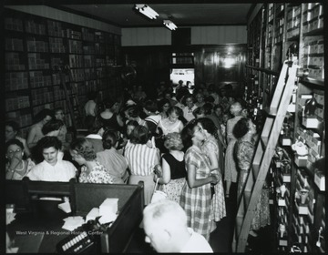 Interior of the store located on Temple St. A crowd looks through the store to examine products for sale. Subjects unidentified.