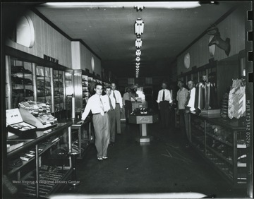 "Gentleman third from the left is identified as ""Punchy"" Neely. The rest are unidentified. Interior of the store located on Temple Street."
