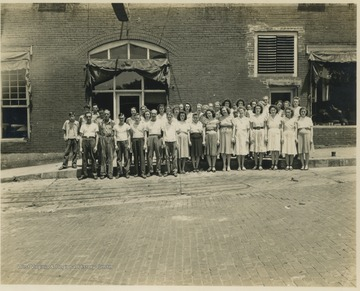 Employees pose for a group picture beside the building located on 2nd Avenue. Subjects unidentified.