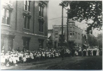 A crowd gathers on the street beside the First National Bank of Hinton building. Subjects unidentified.