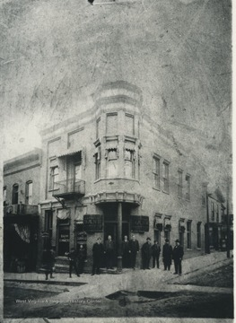 The bank staff pose in front of the building located on 3rd Avenue. Subjects unidentified.