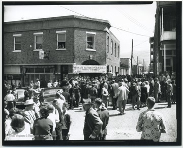 "A crowd surrounds the building located on 3rd Avenue. The sign at the entrance reads, ""Building and All Stock and Fixtures To Be Sold at Absolute Auction, Saturday at 10:00 a.m."" Subjects unidentified."