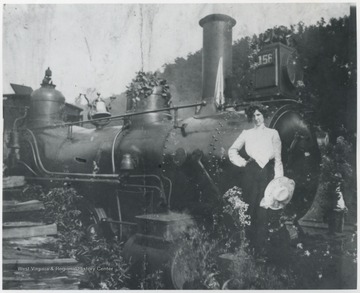 Mary Murrell, married to R. O. Murrell, poses beside the engine.