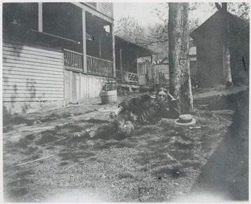 Murrell is pictured in his yard under a tree. Original photo is captioned  'Sleeping Beauty'. The house is located at the corner of 5th Avenue and Summers Street. Note the side porches.