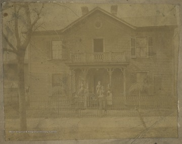 Family pictured in front of the house. Subjects unidentified.