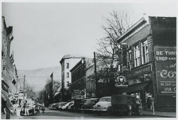 Parked cars line the street in front of the store buildings. A. W. Cox Department Store pictured on the right.
