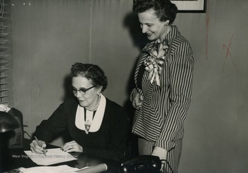 "Caption on back of photograph reads: ""Picture taken at Weston as Mrs. Davis signs oath of office as only woman member of State Advisory Board Department of Public Assistance. After Mrs. Rush Holt, Secretary of State, administered the oath."""