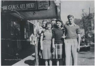 "Pictured from left to right in the front is Earnett Cobb, Betty Jane Arrington Angell, and Lloyd Seldomridge. The two gentleman in the back are Homer Thrall, left, and Raymond W. Argabright. On the awning, above the group, reads, ""The Gang's All Here""."