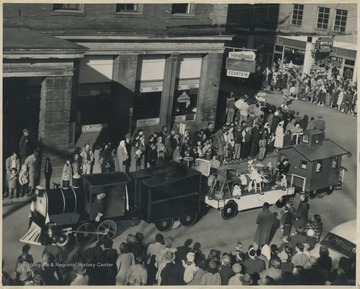 A crowd gathers on the sidewalks as a float in the parade travels through the corner of Ballengee Street and 2nd Avenue.