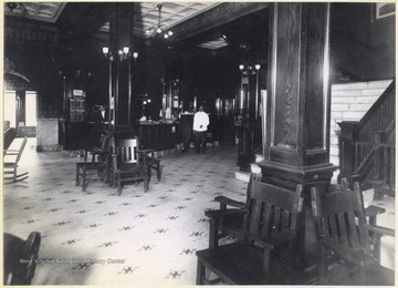 Interior of the hotel. An unidentified employee stands behind the counter next to a schedule of trains.
