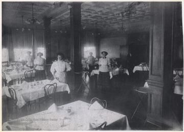 Female employees pose by the set tables around the room. Subjects unidentified.