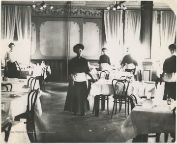 Female employees pose by the set tables.Subjects unidentified.